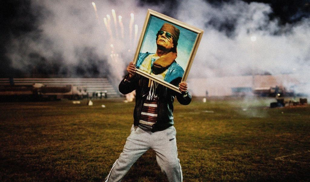 Image: Moises Saman. Libya, Zawiyah 2011. A Qaddafi supporter holds a portrait of the Libyan leader during a celebration. Copyright Moises Saman~Magnum Photos