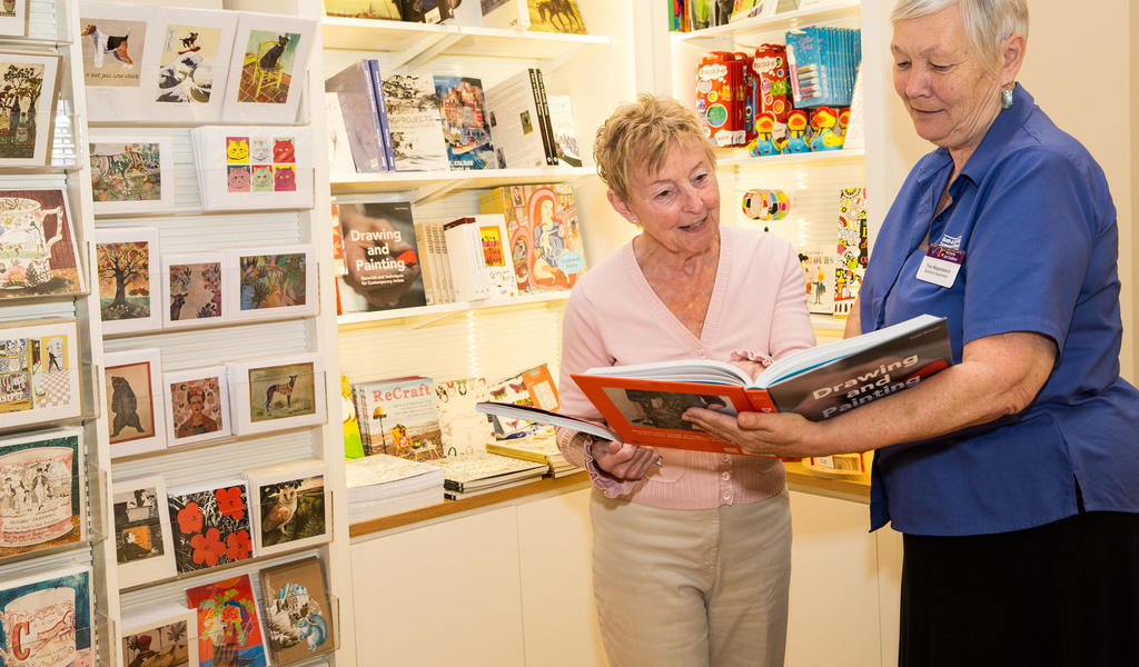 Image: A visitor looking at a book in the shop