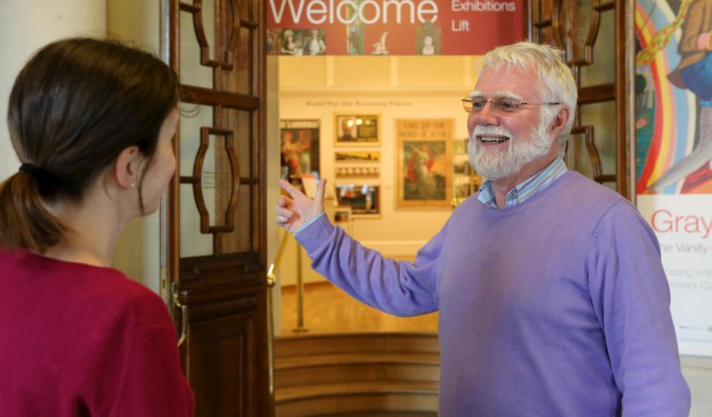 Image: A volunteer welcoming a visitor