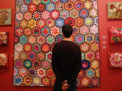 Image: A visitor viewing a Kaffe Fassett quilt