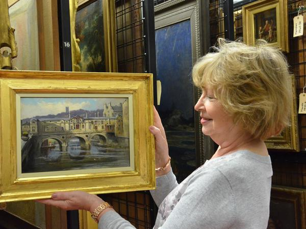 Image: Christine Milne holding the restored adopted painting of 'Pulteney Weir' by John Fullylove.